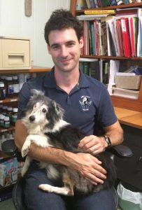 Image of Neil Barnsley holding Sheltie client, Poppy, who was suffering from brachial plexus injury